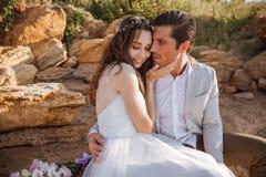 Романтичные пожененные пары сидя на пляже Стоковая Фотография RF
