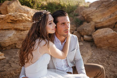 Романтичные пожененные пары сидя на пляже Стоковая Фотография
