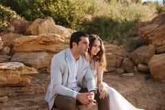 Романтичные пожененные пары сидя на пляже Стоковые Изображения RF