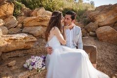 Романтичные пожененные пары сидя на пляже Стоковое Фото