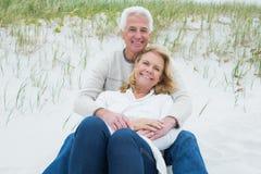 Романтичные старшие пары ослабляя на пляже Стоковые Изображения