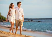 Романтичные счастливые пары идя на пляж на заходе солнца Стоковые Фотографии RF