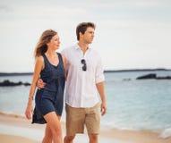 Романтичные счастливые пары идя на пляж на заходе солнца Стоковая Фотография