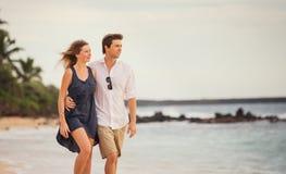 Романтичные счастливые пары идя на пляж на заходе солнца Стоковое Изображение RF