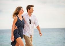Романтичные счастливые пары идя на пляж на заходе солнца Стоковые Изображения RF
