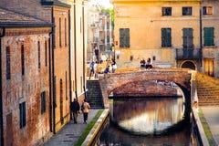 Романтичные убежища в Италии греют света тона на заходе солнца над зданиями и мостом красных кирпичей старыми на канале Comacchio Стоковая Фотография