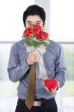 Романтичный бизнесмен с букетом и подарочной коробкой Стоковое Фото