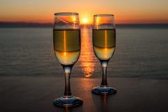 Романтичный вечер, заход солнца, 2 рюмки, путь солнца на воде между 2 рюмками с вином Стоковая Фотография