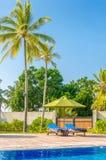 Романтичный взгляд 2 sunbeds на бассейне Стоковое Фото