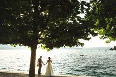 Романтичный жених и невеста пар новобрачных на пляже захода солнца около se Стоковые Изображения