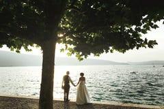 Романтичный жених и невеста пар новобрачных на пляже захода солнца около se Стоковая Фотография