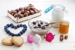 Романтичный завтрак овсяной каши, голубик, меда, молока и печениь Стоковые Фото