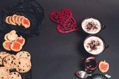 Романтичный завтрак 2 чашки кофе, капучино с печеньями шоколада и печенья около красных сердец на черной предпосылке таблицы Стоковая Фотография RF