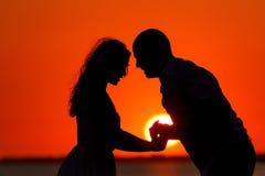 Романтичный заход солнца и силуэты любовников Стоковая Фотография