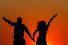 Романтичный заход солнца и силуэты любовников стоковое фото