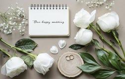 Романтичный модель-макет с цветками и тетрадью на бежевой предпосылке Стоковая Фотография