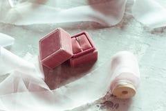 Романтичный настоящий момент: розовая коробка бархата с лентами сатинировки обручального кольца и света на серой предпосылке стоковое фото rf