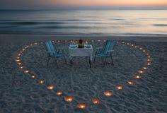 Романтичный обедающий на пляже моря с сердцем свечки Стоковое Изображение RF