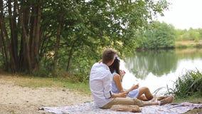 Романтичный пикник молодой пары в влюбленности в лесе около озера акции видеоматериалы