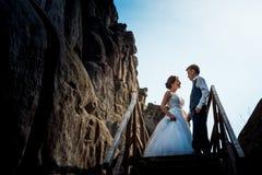 Романтичный портрет красивых усмехаясь новобрачных держа руки около деревянных лестниц около утеса Стоковая Фотография