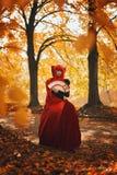 Романтичный портрет красной женщины волос в красном ярком платье при вентилятор сделанный играя карточек Ферзь сердец принципиаль стоковая фотография