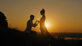 Романтичный силуэт человека получая вниз на его колене и предлагая к женщине на высоком холме - пара получает включенной на заход сток-видео