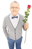 Романтичный старший джентльмен держа розу и смотря камеру Стоковые Изображения