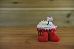 Романтичный торт чашки в розовом и белом при миниатюрный figurine персоны держа доску знака на верхней части и красных сердцах вл Стоковое фото RF