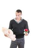 Романтичный человек выбирая между цветками и плюшевым медвежонком Стоковое фото RF