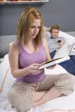 Роман чтения женщины в спальне Стоковое Изображение RF