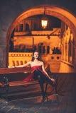 Роскошная женщина в городе платья вечера вечером роскошное ожидание женщины на стенде стоковое изображение