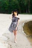 Роскошная женщина перемещения в черно-белом beachwear идя принимающ прогулку на пляже лета песка Турист девушки на лете Стоковое Фото