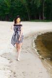 Роскошная женщина перемещения в черно-белом beachwear идя принимающ прогулку на пляже лета песка Турист девушки на лете Стоковые Фото