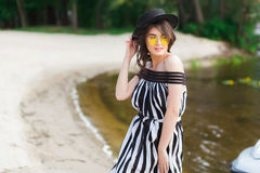 Роскошная женщина перемещения в черно-белом beachwear идя принимающ прогулку на пляже лета песка Турист девушки на лете Стоковое Изображение RF
