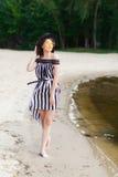 Роскошная женщина перемещения в черно-белом beachwear идя принимающ прогулку на пляже лета песка Турист девушки на лете Стоковое фото RF