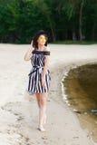 Роскошная женщина перемещения в черно-белом beachwear идя принимающ прогулку на пляже лета песка Турист девушки на лете Стоковые Изображения RF