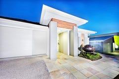 Роскошная лицевая сторона особняка с белыми стенами и гаражом Стоковые Фотографии RF