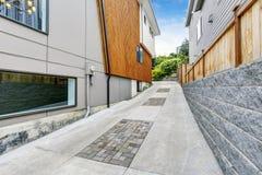 Роскошная подъездная дорога к гаражу около современного дома с деревянной отделкой панели Стоковое фото RF