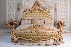 Роскошная спальня в светлых цветах с золотыми деталями мебели Большая удобная двойная королевская кровать в элегантной классике Стоковые Фотографии RF