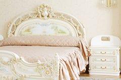 Роскошная спальня с белыми двуспальной кроватью и прикроватным столиком Стоковое фото RF