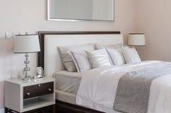 Роскошная спальня с белыми классическими лампой и часами на таблице Стоковая Фотография