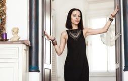 Роскошная темн-с волосами женщина в черном платье и массивнейших ювелирных изделиях золота стоит в входе Стоковая Фотография RF