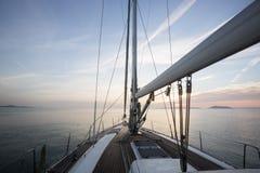 Роскошное плавание парусника в море во время захода солнца Стоковые Изображения