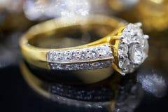 Роскошные кольца с бриллиантом ювелирных изделий золота с отражением на черноте Стоковые Изображения