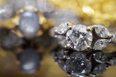 Роскошные кольца с бриллиантом ювелирных изделий золота с отражением на черноте Стоковые Фото