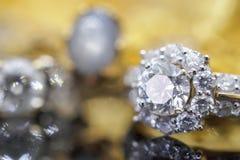 Роскошные кольца с бриллиантом ювелирных изделий золота с отражением на черноте Стоковое фото RF