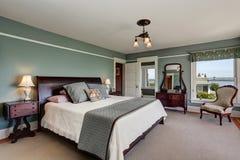 Роскошный интерьер спальни в голубых тонах и королевской кровати Также совершенный взгляд воды Стоковое Изображение