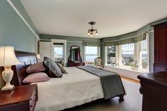 Роскошный интерьер спальни в голубых тонах и королевской кровати Также совершенный взгляд воды Стоковая Фотография