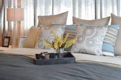 Роскошный интерьер спальни с striped подушками и декоративный комплект чая на кровати Стоковое Фото
