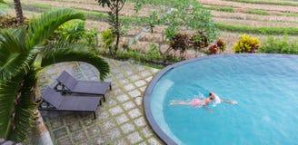 Роскошный курорт Человек ослабляя в воде бассейна безграничности Красивая счастливая здоровая мужская модель наслаждаясь перемеще стоковые изображения